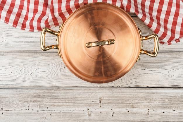 Flatlay van koper kokende pot op houten achtergrond