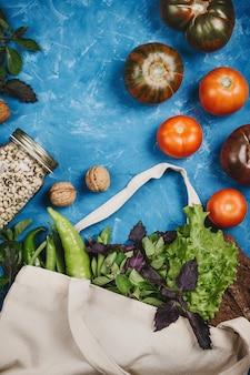 Flatlay van tomaten, groenen in eco zak en bonen in een pot, nul afval kruidenierswaren concept