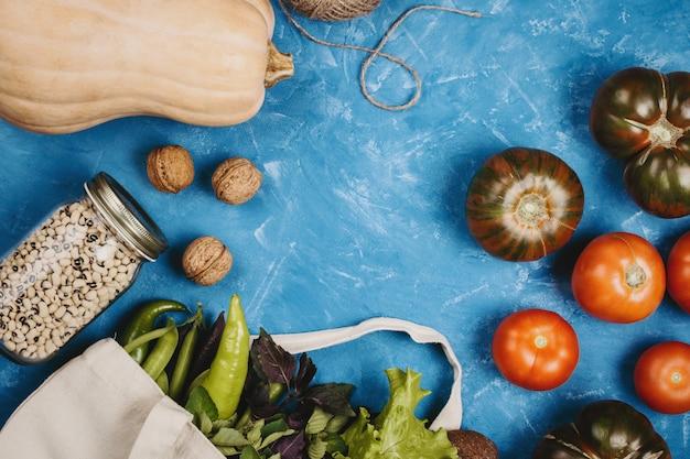 Flatlay van tomaten, groenten, pompoen, touw en bonen in een pot, nul afval boodschappen concept