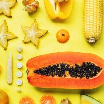 Flatlay van verschillende gele en oranje groenten en fruit samen geknoopt