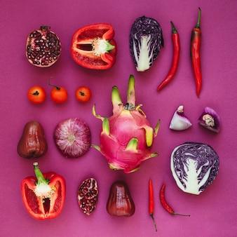 Flatlay van verschillende rode, paarse en roze groenten en fruit samen geknoopt
