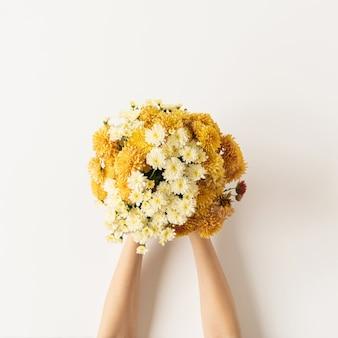 Flatlay van vrouwelijke handen met geel en gember vallen wilde bloemen boeket op wit