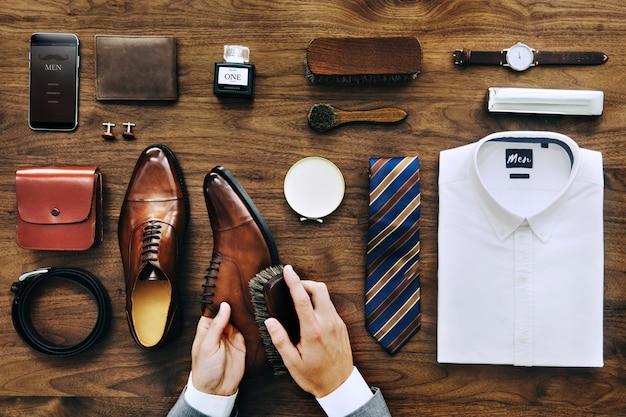 Flatlaymening van een zakenman die zijn schoenen en zijn bezittingen schoonmaakt