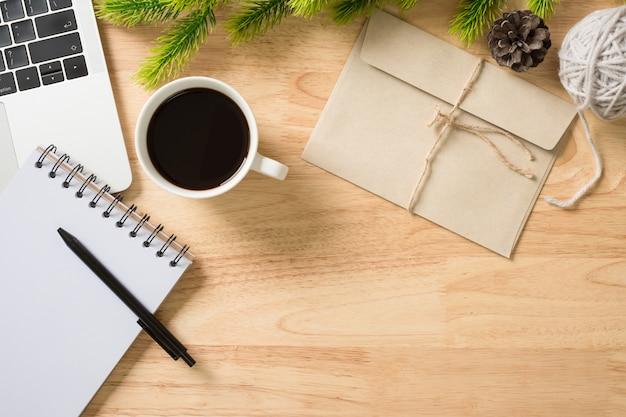 Flay lay, bovenaanzicht kantoor tafel bureau met computer, notitieblok, koffie, pen, bladeren grenen en envelop