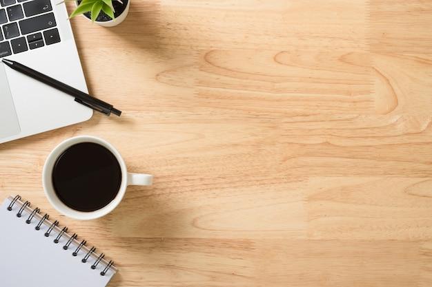Flay lay, bovenaanzicht kantoor tafel bureau met laptop, toetsenbord, koffie, pen en groene plant