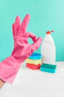 Fles afwassen, sponzen en roze rubberen handschoenen op witte houten tafel op groene muur