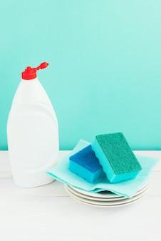 Fles afwassen, sponzen, keukengerei op witte houten tafel op groene muur