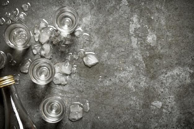 Fles alcoholische drank met glazen en ijs.