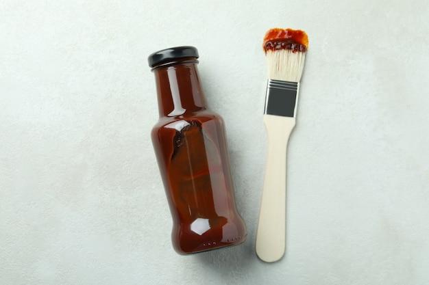 Fles barbecuesaus en penseel op geweven wit