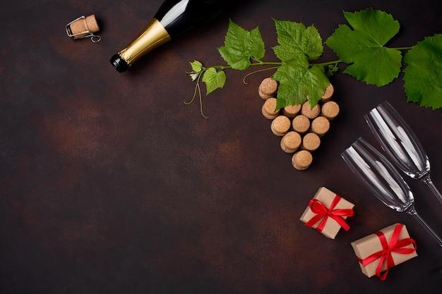 Fles champagne, druivenbos van cork met bladeren, de doos van de wijnglasgift op roestige achtergrond