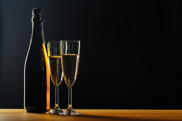 Fles champagne en glazen over donker