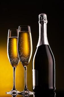 Fles champagne en glazen over donkere oppervlakte