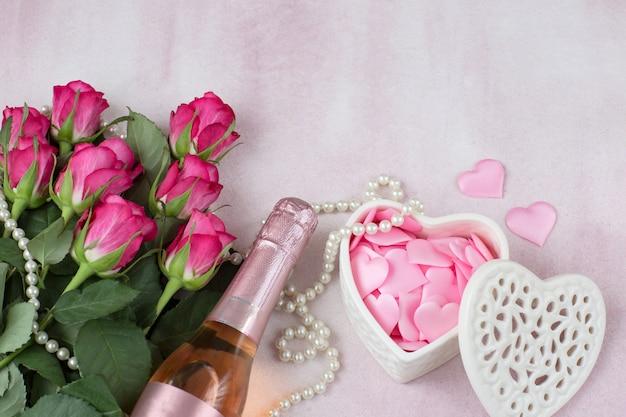 Fles champagne, hartjes in een kistje, een boeket roze rozen en parel kralen