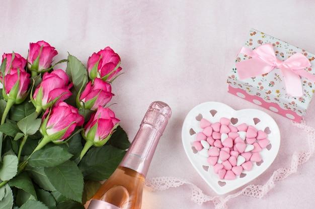 Fles champagne, hartvormige snoepjes, een boeket roze rozen en een cadeau in een doos