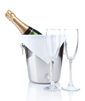 Fles champagne in emmer en lege glazen, geïsoleerd op wit