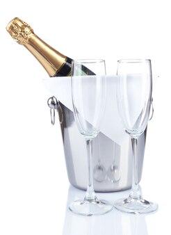 Fles champagne in emmer en lege glazen geïsoleerd