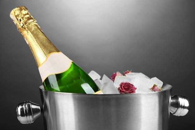 Fles champagne in emmer met ijs, op grijze ondergrond