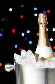 Fles champagne in emmer met ijs, op zwarte ruimte met kleurenlichten