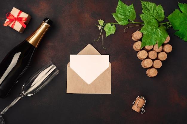 Fles champagne, kloof bos van kurk met bladeren, wijnglas twee, geschenkdoos, envelop en brief op roestige achtergrond.
