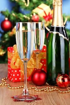 Fles champagne met glazen en kerstballen op houten tafel boven kerstboom