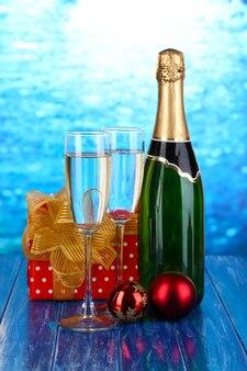 Fles champagne met glazen en kerstballen op houten tafel op blauwe achtergrond
