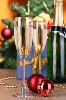 Fles champagne met glazen en kerstballen op houten tafel op kerstboomachtergrond