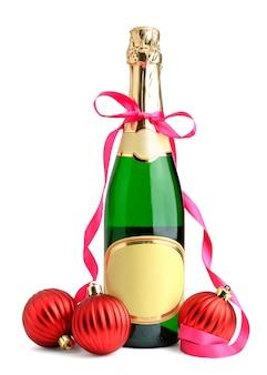 Fles champagne met lint en kerstmisballen die op wit worden geïsoleerd