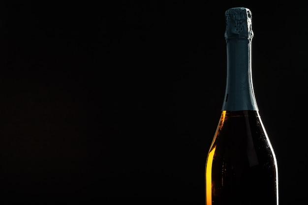 Fles champagne op zwarte achtergrond.
