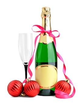 Fles champagne, wijnglas en kerstballen geïsoleerd op wit