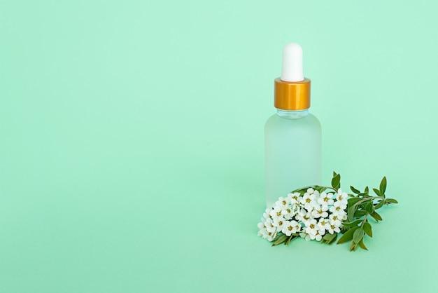 Fles cosmetische pipet met olie en bloemen