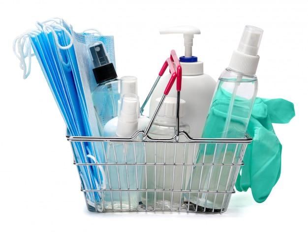 Fles crème, lotion, ontsmettingsmiddel of vloeibare zeep, latex rubberen handschoen en beschermend masker in winkelmandje mand op witte tafel