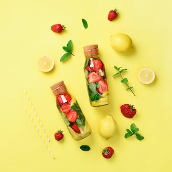 Fles detoxwater met munt, citroen, aardbei op gele achtergrond.