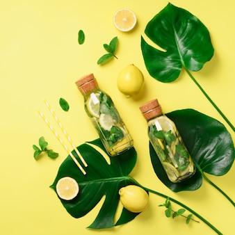 Fles detoxwater met munt, citroen en tropische monsterabladeren op gele achtergrond.