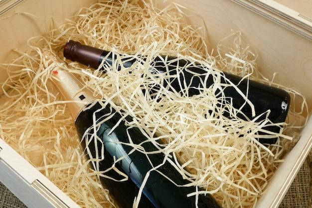 Fles dure elitewijn in een houten kist