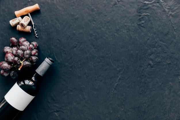 Fles en druif in de buurt van kurkentrekker en kurken