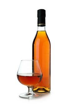 Fles en glas cognac geïsoleerd op witte achtergrond