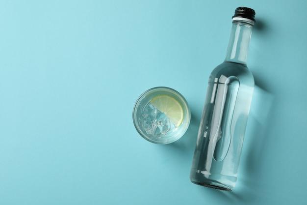 Fles en glas drank met limoen op blauwe muur