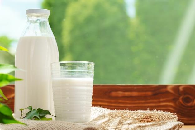 Fles en glas melk op houten tafel tegen wazig gebladerte