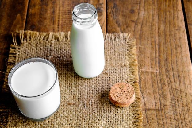 Fles en glas melk op houten tafel