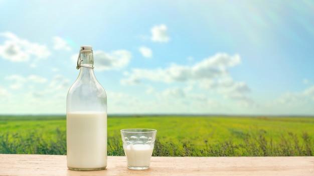Fles en glas met verse melk op een achtergrond van groene weide en blauwe hemel. kopieer ruimte. brede banner