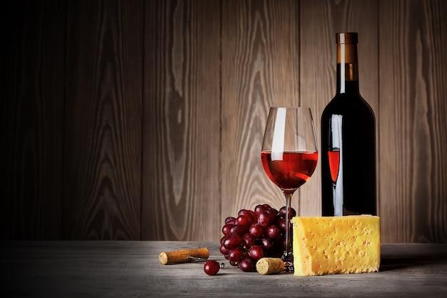 Fles en glas rode wijn met kaas druiven en kurkentrekker
