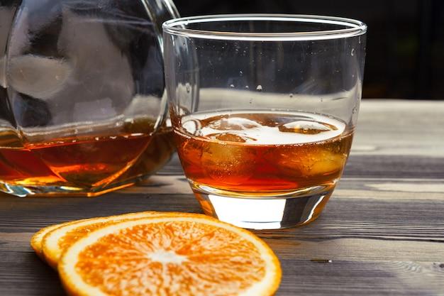 Fles en glas whisky op een houten achtergrond