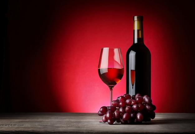 Fles en glas wijn met druiven
