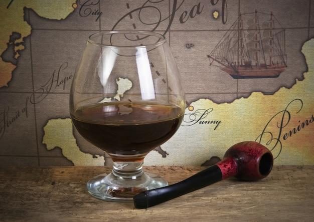 Fles en glas wijn op de achtergrond van oude kaarten