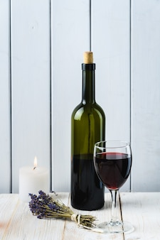 Fles en glas wijn op een witte houten achtergrond. rustieke stijl.