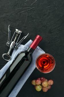 Fles en glas wijn, tros roze druiven en metalen kurkentrekker op donkere achtergrond. bovenaanzicht, kopie-ruimte.