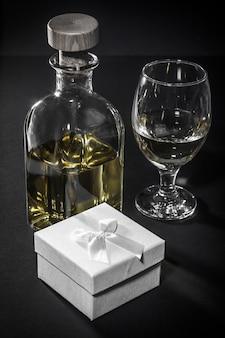 Fles en glas witte wijn, geschenkdoos op zwarte achtergrond. valentijnsdag wenskaart concept.