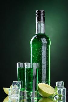 Fles en glazen absint met limoen en ijs