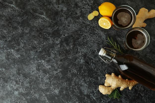 Fles en glazen gemberbier en ingrediënten op zwarte rokerig