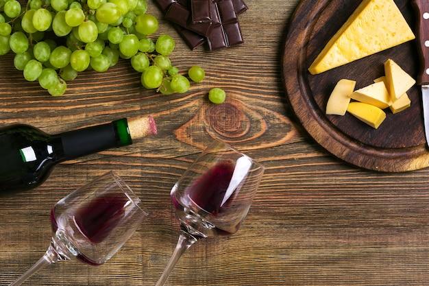 Fles en glazen wijn, kaas en rijpe druiven op houten achtergrond. bovenaanzicht. ruimte kopiëren. plat leggen. stilleven